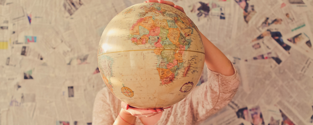 A person holding a large globe planning to work somewhere overseas