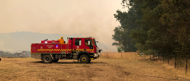 A Wodonga West fire truck watches over a landscape choked by smoke.