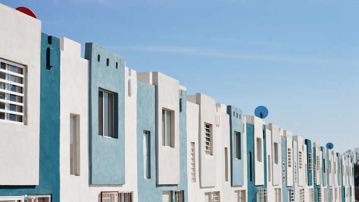 A line of townhouses that are blue and white