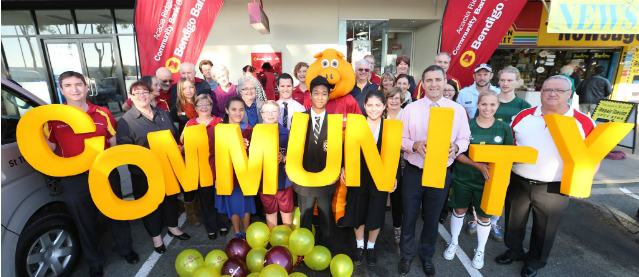 Acacia Ridge Community Bank supporters hold big yellow letters spelling out the word community.