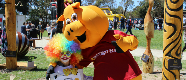 Balnarring Community Bank Branch mascot, a big yellow pig, with a little boy dressed as a clown at a community event supported by the branch.