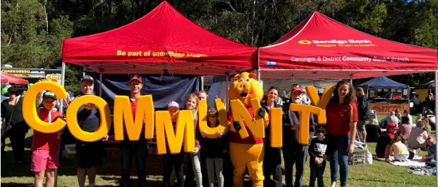 People at a local event sponsored by Canungra Community Bank Branch holding large yellow letters spelling out the words community.