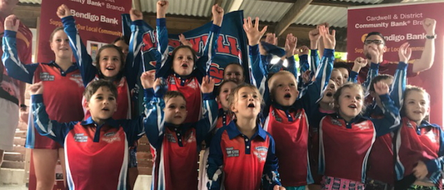 Kids from a sports club cheering with arms in the air after receiving funding from Cardwell Community Bank Branch.