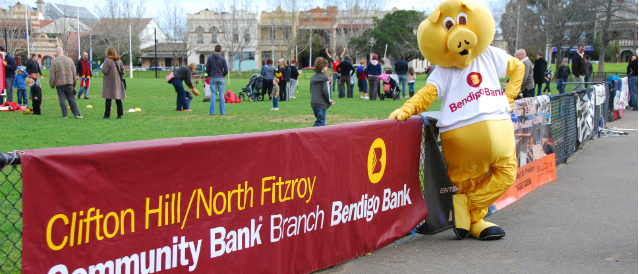 Clifton Hill Community Bank Branch mascot a big yellow pig standing at the boundary line of a local sports ground with a 'proudly supported by Clifton Hill Community Bank Branch' banner.