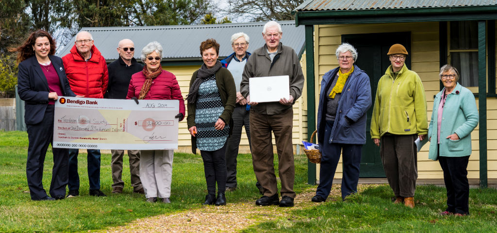 Representatives from Trentham Historical Society pictured holding a novelty cheque presented by a branch staff member.