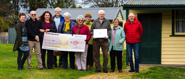 Historical Society of Trentham standing outdoors together holding a Bendigo Bank novelty cheque.