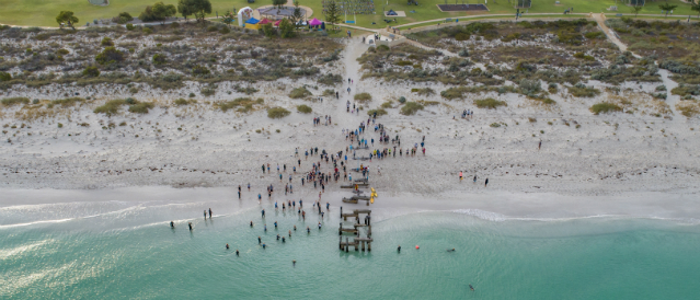 Aerial shot of an event sponsored by the local Community Bank Branch held at the beach shows competitors running from the sand to the water.