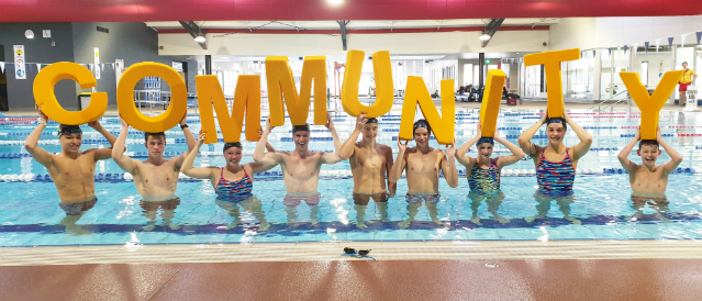 Warragul swimming pool with swimmers holding COMMUNITY letters