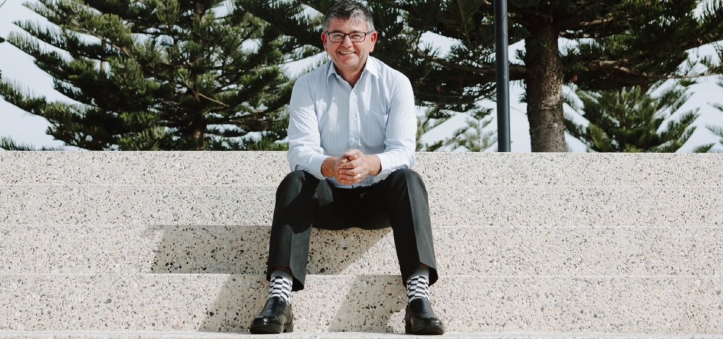Image of David, Branch Manager of Busselton and Dunsborough Community Bank branches of Bendigo Bank, sitting outdoors on large steps with trees in the background.