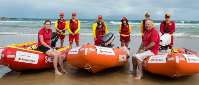 Freshwater Community Bank branch staff and directors with members of the local surf lifesaving club at beach sitting and standing around International Rescue Boats funded by the Community Bank Branch.