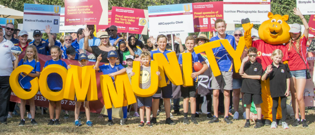 Representatives of the Heidelberg and East Ivanhoe communities holding yellow COMMUNITY letters and sponsorship signs provided by Bendigo Bank.