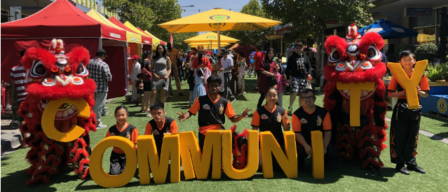 Chinese dragons and people holding large yellow letters spelling the word 'community' at an event funded by Altona and Laverton Community Bank branches.