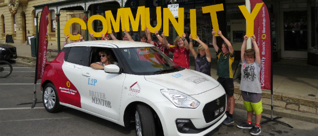 Local car used for youth driver education and funded by Beechworth Community Bank branch with people standing holding big yellow letters spelling out the word 'community'.