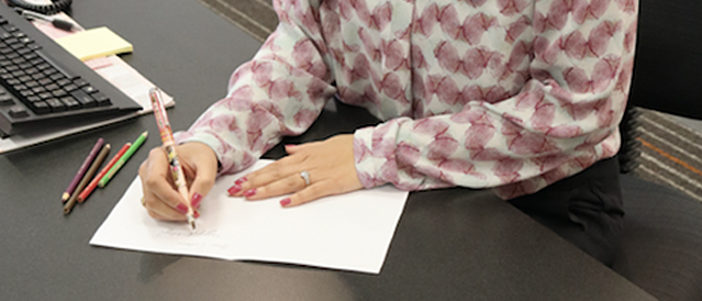 A Bendigo Bank staff member handwriting a greeting card