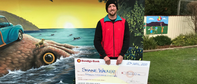 Artist funded by Sheffield Ralton Community Bank Branch standing in front of his mural with a large novelty cheque.