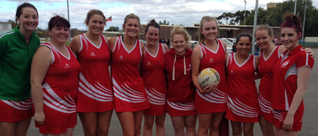 Netballers standing in a group with a ball on the netball court after receiving funding from Elmore, Lockington and Rochester Community Bank Branch funding.