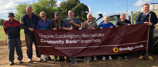 Rochester Cemetery Trust members receive a grant and stand with a Elmore, Lockington, Rochester Community Bank Branch banner at the local cemetery.