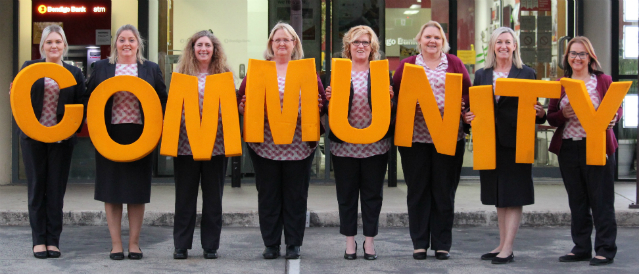 Staff of Jimboomba branch holding COMMUNITY letters out front of the branch.