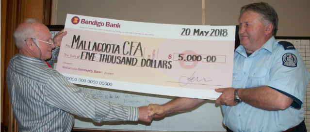 Representative from the Mallacoota CFA receives a cheque from a director of Mallacoota Community Bank Branch.