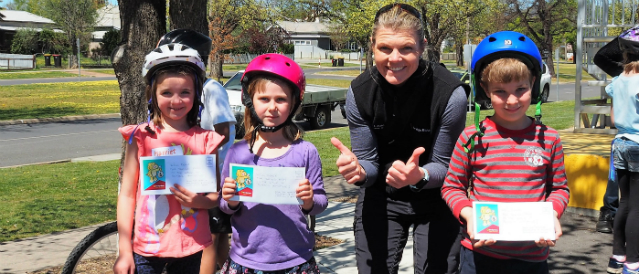 Three children wearing bike helmets and standing in front of their bikes while holding up congratulations certificate with a Mansfield Community Bank Branch director.