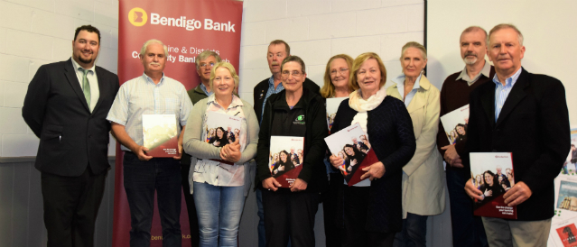People standing in the Deloraine Community Bank Branch holding their cheques.