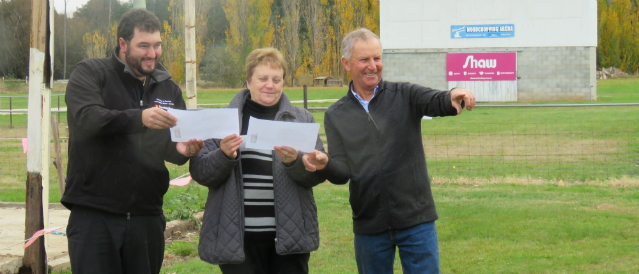 Three people standing on a sports ground holding plans for a redevelopment resulting from funding from Deloraine Community Bank Branch.