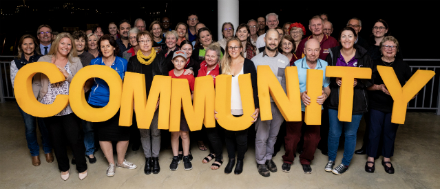 Grant recipients gather with Geraldton Community Bank Branch staff and directors to celebrate a round of Community Bank grants. Group holds up big yellow letters spelling the word 'community'.