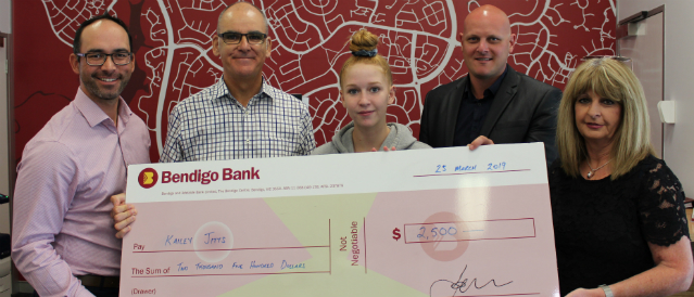 Young person who received a scholarship with Community Bank directors and branch staff holding a large, novelty cheque.