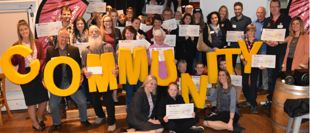 A group of people holding big yellow letters spelling the word 'community' and cheques celebrating a grants program run by Monbulk Community Bank Branch.