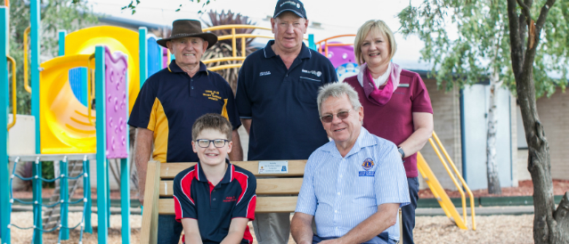 Mount Gambier Community Bank Branch Manager with Men's Shed members and a child testing out the local primary school's Buddy Bench, built by the Men's Shed members and funded by the local Community Bank branch.