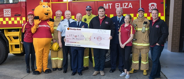 Local community members holding novelty cheque standing with Piggy in front of Mt Eliza CFA Fire Truck.