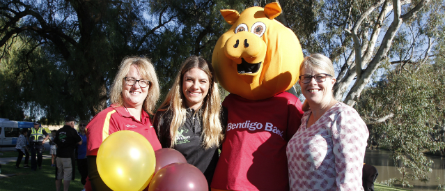 Nathalia Community Bank Branch staff standing at a community event funded by the branch with the Bank's mascot, a big yellow pig.