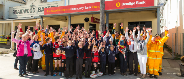 People standing outside Braidwood Community Bank Branch with their hands in the air celebrating Community Bank funding.