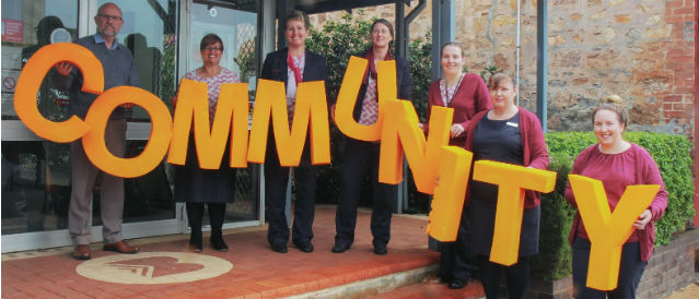 Pingelly Brookton Community Bank Branch staff standing on the steps of the branch holding big yellow letters which spell out the word 'community'.