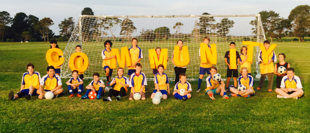 Soccer kids whose club has received Toora and Foster Community Bank Branch funding standing in front of soccer goal holding big yellow letters spelling out the word community.