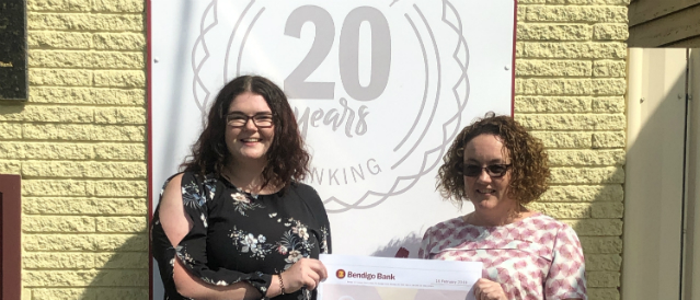 Toora and Foster Community Bank Branch 2019 scholarship recipient with a staff member standing outside the bank branch with a novelty cheque.