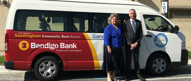 Two people standing next to a bus sponsored by Sandringham Community Bank Branch.