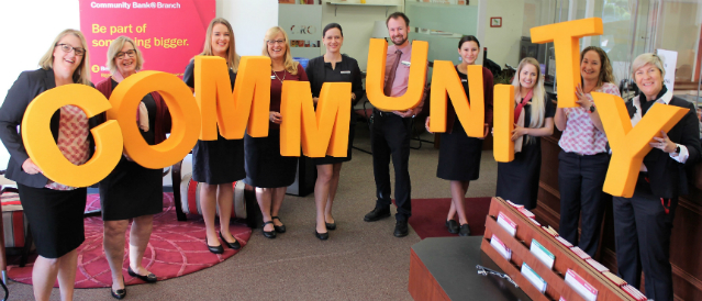 Cooroy branch staff group photo holding COMMUNITY letters.