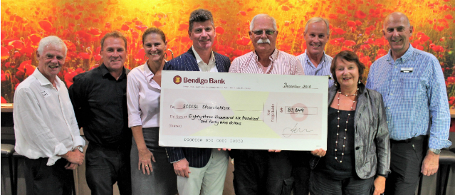 Sunshine Coast Community Financial Services Limited board of directors standing and holding a large novelty cheque.
