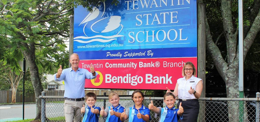 Tewantin State School leaders for 2020 celebrate with principal Rob and Bendigo Bank manager Linda in front of school sign