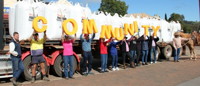 Picture of Toodyay locals standing alongside a truck loaded with hay bales holding up big yellow letters spelling the word 'community' to represent the support of Toodyay Community Bank Branch.