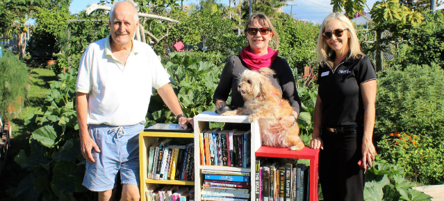 People pictured with a bookshelf of books to promote the new little lending libraries supported by Bendigo Bank Tugun.