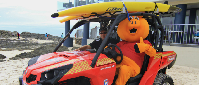 Tugun Community Bank Branch mascot, a big yellow pig, sitting in a beach vehicle to celebrate a grant for the surf life saving club.