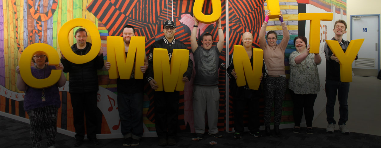 Araluen members standing holding yellow COMMUNITY letters infront of painted mural at the Diamond Creek Disability Support Centre.