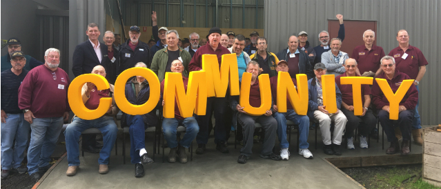 People representing groups which have received Valley Community Financial Services sponsorships standing in a group holding big yellow letters spelling out the word 'community'.