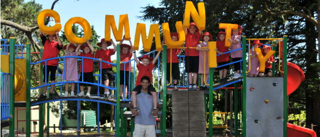 Children standing on a piece of equipment in a playground holding up big yellow letters spelling out the word 'community' to acknowledge a grant for the play equipment from Wandin Seville Community Bank Branch.