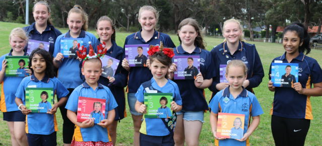 Group of girl guides holding guide handbooks ranging from level one to level five.