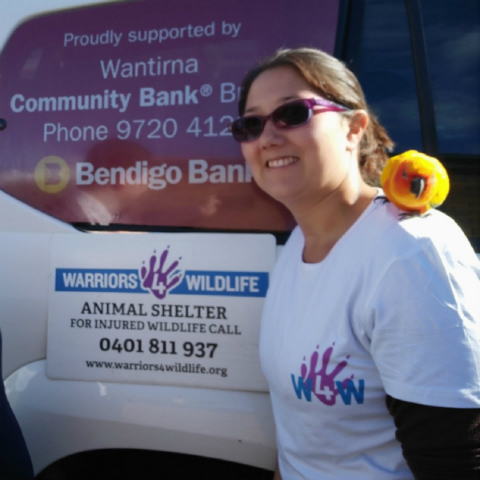 Warriors 4 Wildlife group representative in front of bus branded Wantirna Community Bank Branch of Bendigo Bank and Warriors 4 Wildlife. The group representative has a yellow bird on her shoulder.