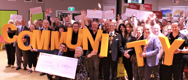 Warrandyte Community Bank Branch representatives holding a novelty cheque during a community event.