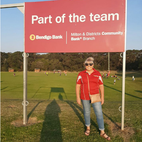 Branch representative standing in front of a Bendigo Bank sponsorship sign.